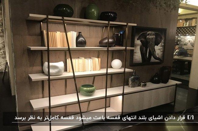 تصویر شلف های سفید و مشکی مقابل دیوار قهوه ای رنگ با نورپردازی و لوازم دکوری کوتاه و بلند