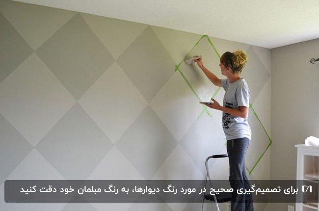 رنگ آمیزی دیوار با طرح لوزی لوزی با تناژ طوسی توسط یک زن