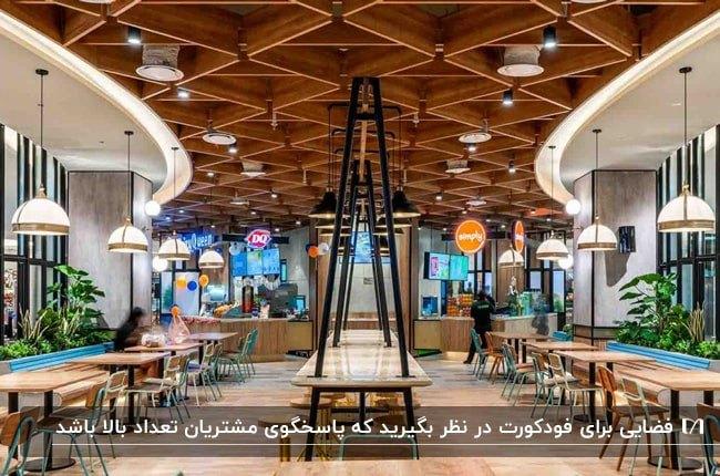 فودکورتی با سقف کاذب چوبی، میز و صندلی های چوبی و لوستر آویز سفید