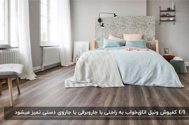 اتاق خوابی با کفپوش وینیل، تخت دو نفره با روتختی سفید و کوسن های آبی و گلبهی