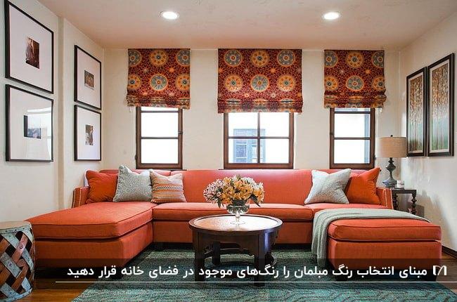 نشیمنی با دیوارهای سفید، مبل یو شکل نارنجی متناسب با رنگ پرده و قاب عکس های روی دیوار