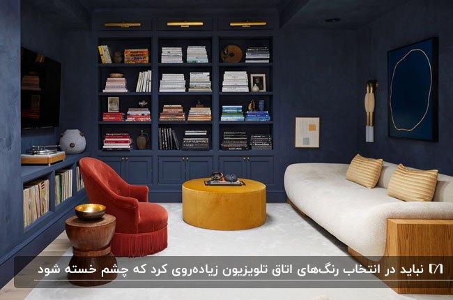 اتاق تلویزیونی با دیوارهای سرمه ای، مبل سفید و زرشکی و پاف خردلی