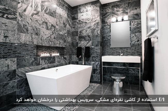 سرویس بهداشتی با کاشی های مشکی و نقره ای و وان و روشویی سفید با آینه مستطیلی