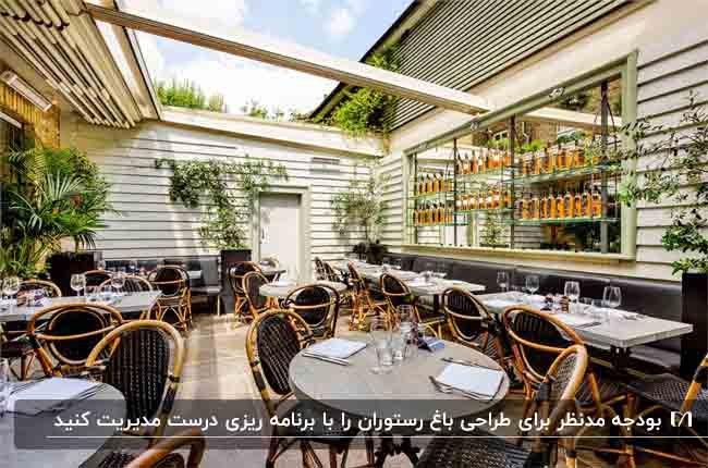 باغ رستورانی با دیوارهای سفید، میزهای گرد و صندلی های ترکیبی چوب با رنگ مشکی