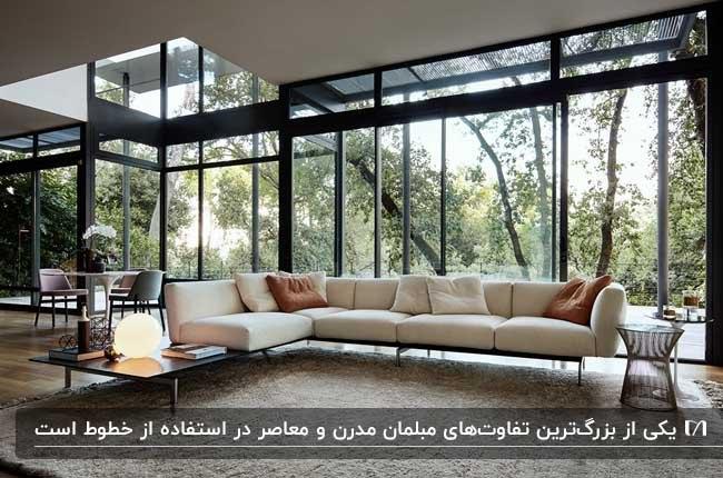 مبلمان مدرن ال شکل کرم رنگ مقابل دیوار شیشه ای با چشم انداز جنگل