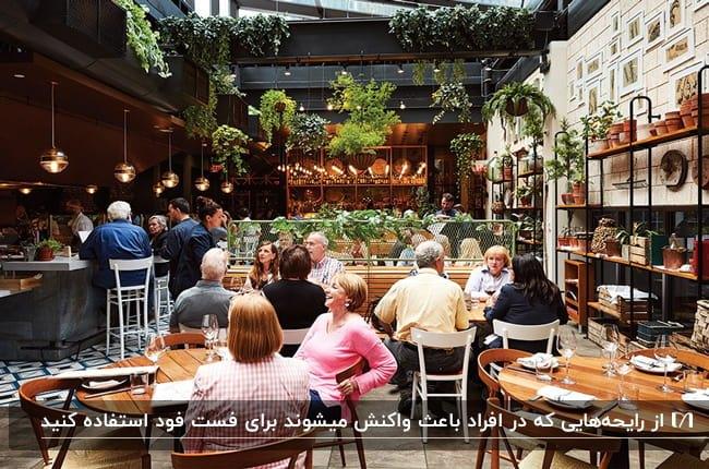 فست فود شلوغی با میز و صندلی های چوبی و سفید با سقف فلزی مشکی