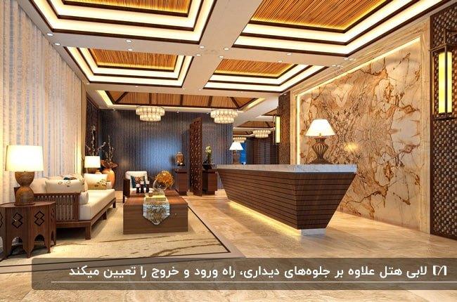 تصویر لابی یک هتل با شکوه با سقف کاذب و نورپردازی و میز رزوشن قهوه ای