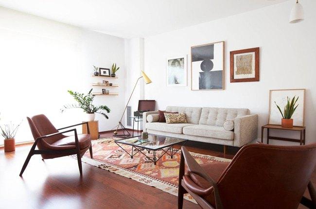 تصویر یک نشیمن مدرن با کفپوش چوبی، کاناپه مدرن کرم رنگ