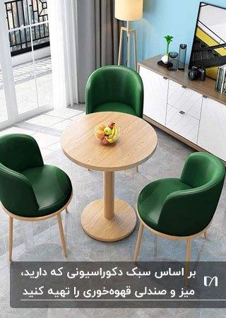 تصویر میز گرد چوبی و صندلی های سبز رنگ برای قهوه خوری