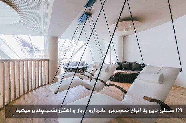 تصویر بالکنی با کفپوش و حفاظ چوبی و سه صندلی ریلکسی دیواری سفید رنگ