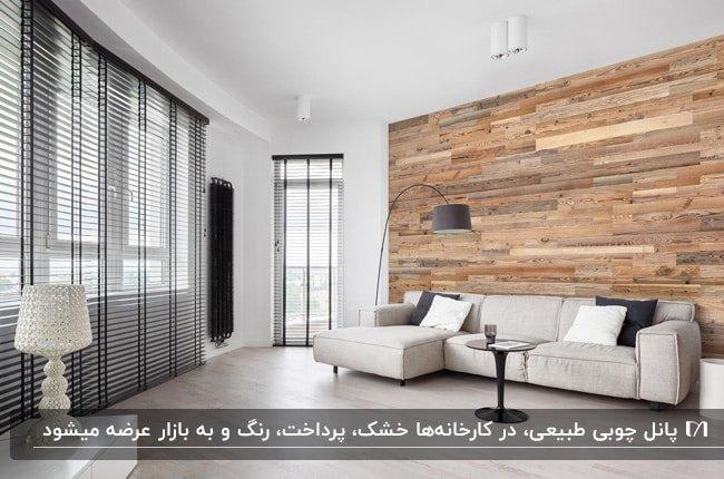 نشیمن مینیمالی با دیوار چوبی، مبل ال شکل کرم و آباژور پایه بلند منحنی مشکی