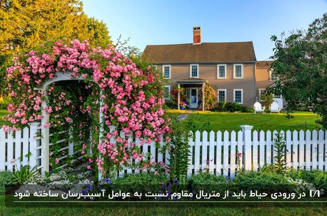تصویر نمای خارجی حیاط خانه قهوه ای دوطبقه ای با حفاط و درب سفید با گلهای صورتی