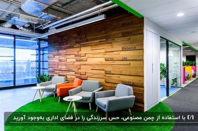 اداره ای با صندلی های طوسی و نارنجی، کفپوش چمن مصنوعی مقابل دیوارپوش چوبی