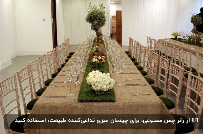 میزغذاخوری بزرگی با صندلی هایش به رنگ سبز و کرم با رانر چمن مصنوعی