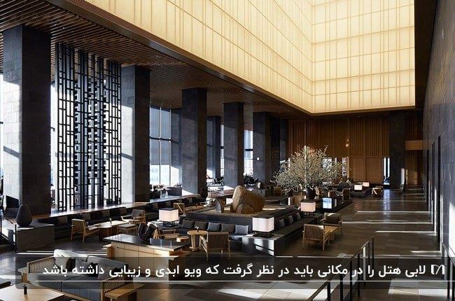 لابی بزرگ هتلی مجلل با دیوارپوش ها چوبی و ستون های مشکی با چشم انداز زیبا