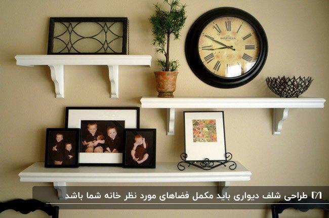 تصویری از شلف های سفید روی دیوار کرم رنگ به همراه قاب های عکس، ساعت و گلدان گل