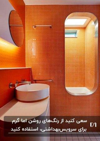 سرویس بهداشتی با دیوارهای نارنجی رنگ و روشویی و کابینت سفید با آینه هندسی به همراه نورمخفی