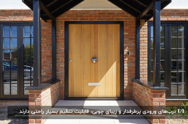 خانه ای با نمای آجری قرمز، ستون ها و فریم درب و پنجره مشکی با درب ورودی چوبی