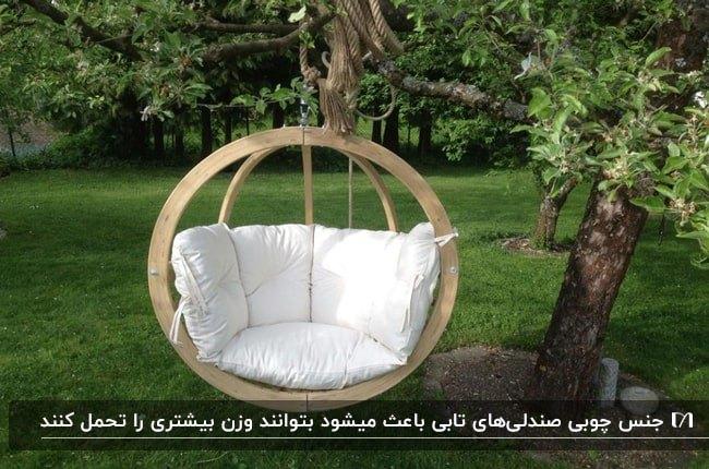 تصویر یک صندلی تابی گرد چوبی با تشکچه و کوسن های سفید آویزان شده از درخت