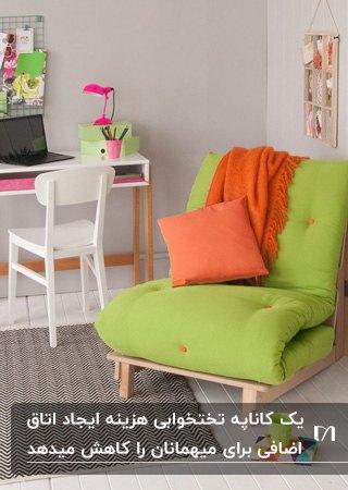 اتاق خوابی با میز تحریر چوبی و صندلی سفید و صندلی تخت خواب شو چوبی با تشک سبز و کوسن نارنجی