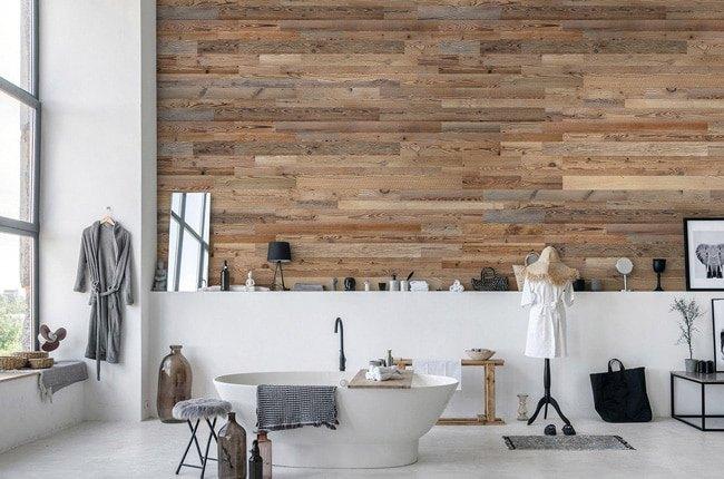سرویس بهداشتی مدرنی با اکسسوری های طوسی و سفید، وان بیضی و دیوار چوبی