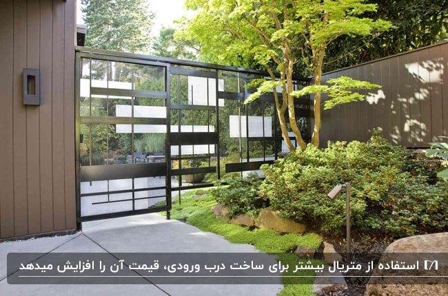 تصویر درب ورودی ترکیبی از شیشه و فلز مشکی برای حیاط ویلایی با دیوارهای قهوه ای