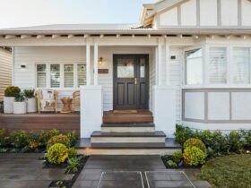 خانه ای با نمای سفید، ایوانی کوچک با میز و صندلی و درب ورودی قهوه ای تیره