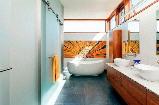 سرویس بهداشتی بزرگی با کابینت روشویی چوبی، دیوار آبی و تابلوی نقاشی زرد رنگ گل آفتابگردان