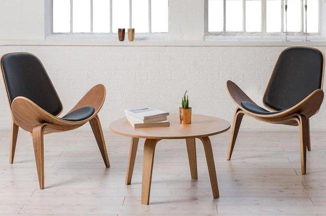 تصویر دو صندلی و یک میز گرد چوبی قهوه خوری با چرم مشکی