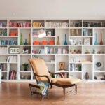 تصویر یک صندلی راحتی کرم و قهوه ای مقابل دیواری با شلف های سفید و روبه روی دیوار شیشه ای