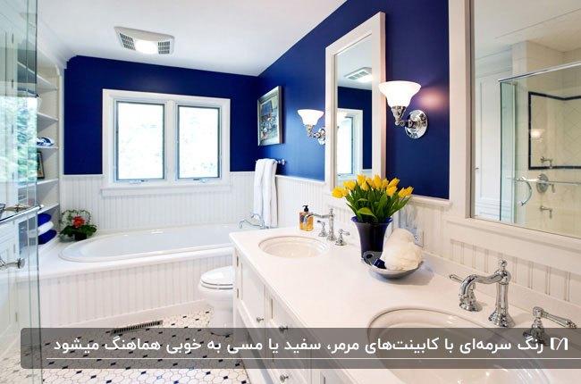 سرویس بهداشتی بزرگ و سفیدی با دو روشویی گرد و دو آینه و دیوارهای تا نیمه سرمه ای
