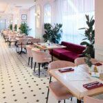 رستورانی با کفپوش سفید و مشکی، میزهای چوبی و صندلی ها و نیمکت های طورتی و بنفش