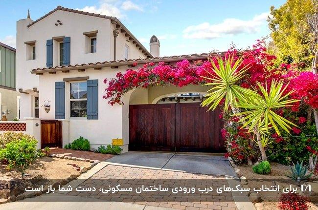 خانه ویلایی دو طبقه ای با نمای سفید، گل های سرخابی و درب ورودی قهوه ای دو لنگه