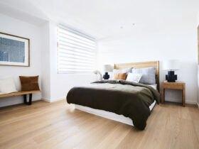 اتاق خواب روشنی با تخت چوبی، روتختی تیره با کوسن های چند رنگ و کفپوش چوبی