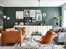 نشیمنی مدرن با دیوارهای سبز تیره و مبلمان چرم عسلی رنگ با تعدادی قاب عکس روی دیوار