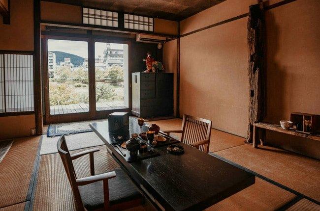 اتاقی با میز ناهارخوری مستطیل شکل قهوه ای ژاپنی مقابل درب شیشه ای رو به طبیعت