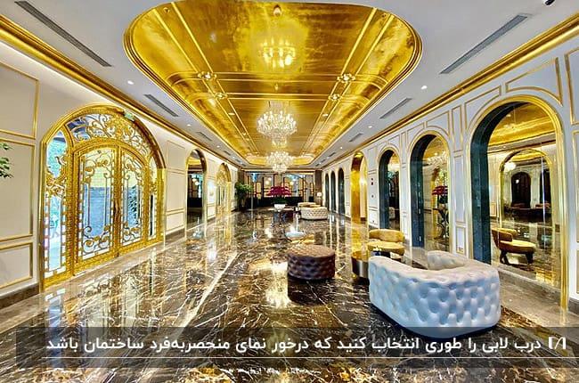 لابی ساختمان مجللی با ترکیب رنگ سفید و طلایی با دربی طلایی و بزرگ