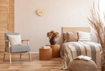 اتاق خوابی به رنگ چوب با تخت کرم، صندلی و دو میز استوانه چوبی