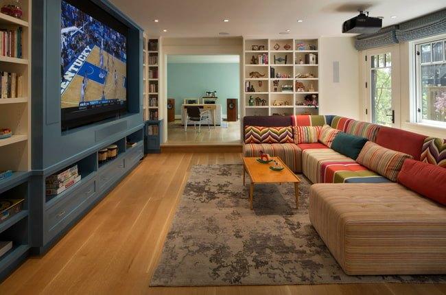 اتاق تلویزیونی با دیوار پشت تلویزیون آبی، مبلمان یو شکل با پارچه رنگی و فرش طوسی