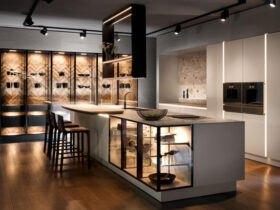 آشپزخانه ای بزرگ با کابینت های کرم رنگ و ویترین های شیشه ای با چراغ ها و چهارپایه کانتر