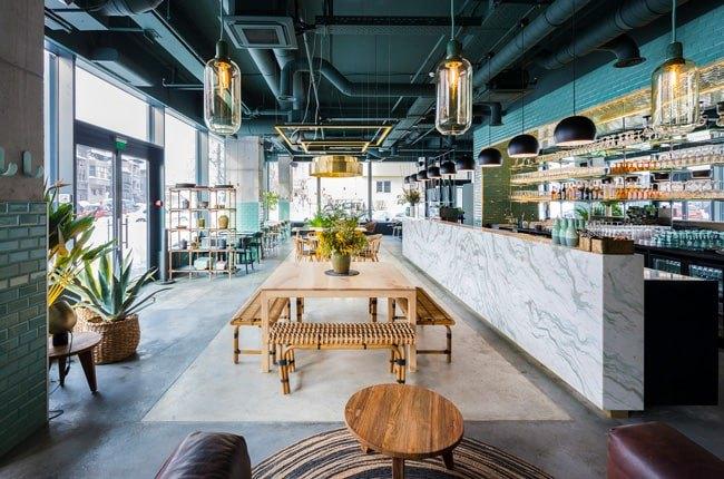 فست فود مدرنی با میز و صندلی های چوبی، سقف لوله کشی آبی تیره و کانتر طوسی