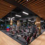 دکوراسیون چوبی و خاکستری یک باشگاه بدنسازی مدرن با لوازم بدنسازی