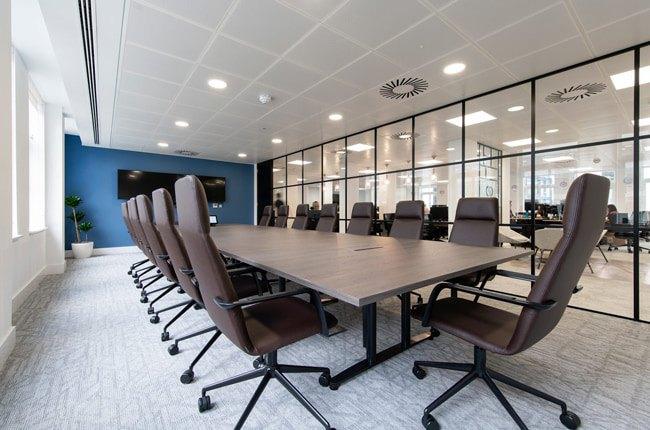 تصویر یک اتاق جلسه در اداره با یک دیوار شیشه ای، میز مستطیلی چوبی و صندلی های اداری قهوه ای
