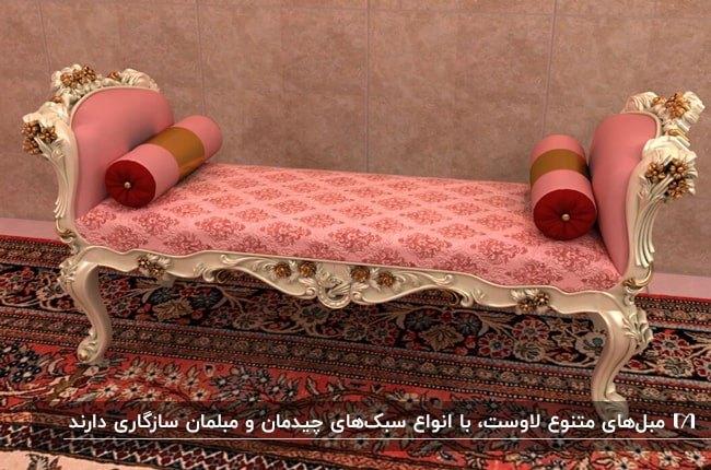 یک مبل لاوست صورتی با فریم سفید و پارچه طرحدار صورتی و زرشکی روی فرش سنتی