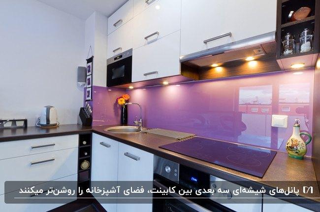 آشپزخانه ای با کابینت های سفید و پنل بین کابینتی شیشه ای بنفش رنگ