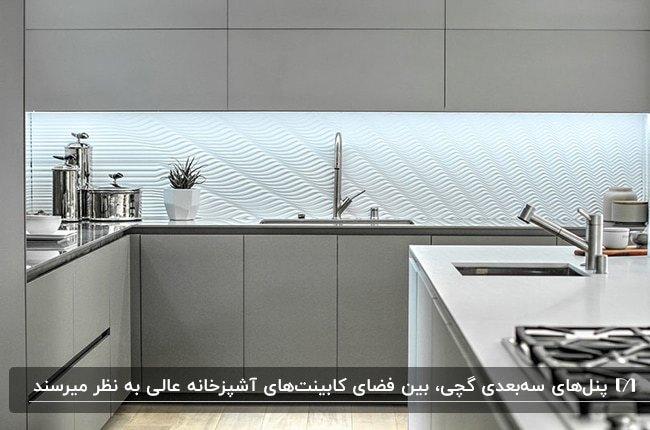 آشپزخانه بزرگی با کابینت های طوسی و پنل بین کابینتی سه بعدی گچی سفید رنگ