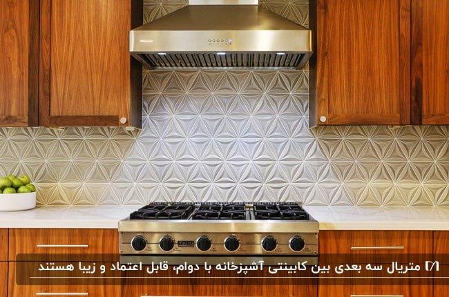 کابینت های چوبی قهوه ای روشن و اجاق گاز و هود نقره ای با پنل دیواری سه بعدی سفید رنگ