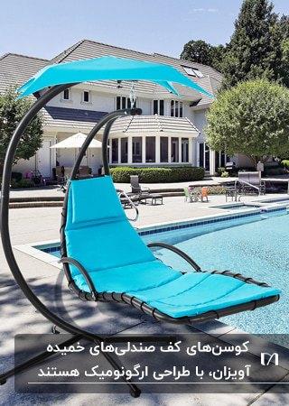 تصویر یک صندلی خمیده آویزان با فریم مشکی و پارچه آبی کنار استخر