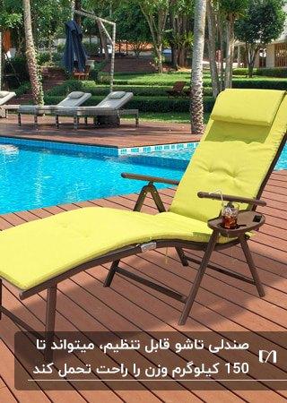 صندلی تاشو قابل تنظیم با فریم قهوه ای و تشکچه سبز فسفری کنار استخری