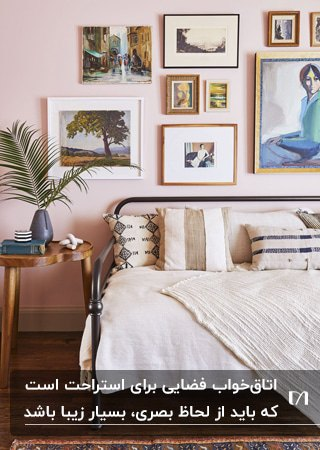 اتاق خوابی با تخت دو نفره، میز پاتختی چوبی و قاب عکس هایی روی دیوار صورتی کمرنگ